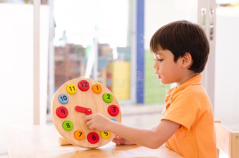 Tempo de aprendizagem do rapaz pequeno com o brinquedo do pulso de disparo do educationa do montessori fotos de stock
