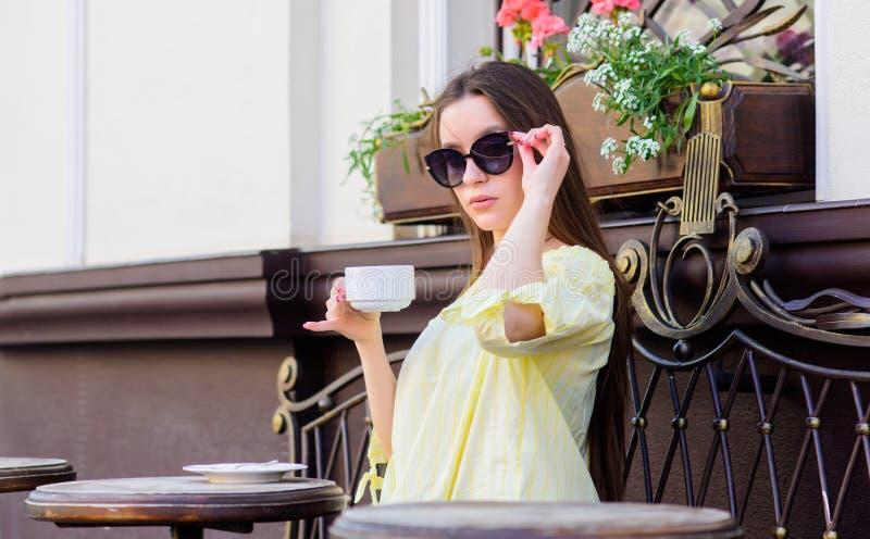 Tempo de caf? da manh? no caf? A menina aprecia o caf? da manh? Data de espera A mulher nos ?culos de sol bebe o caf? fora Menina fotografia de stock royalty free