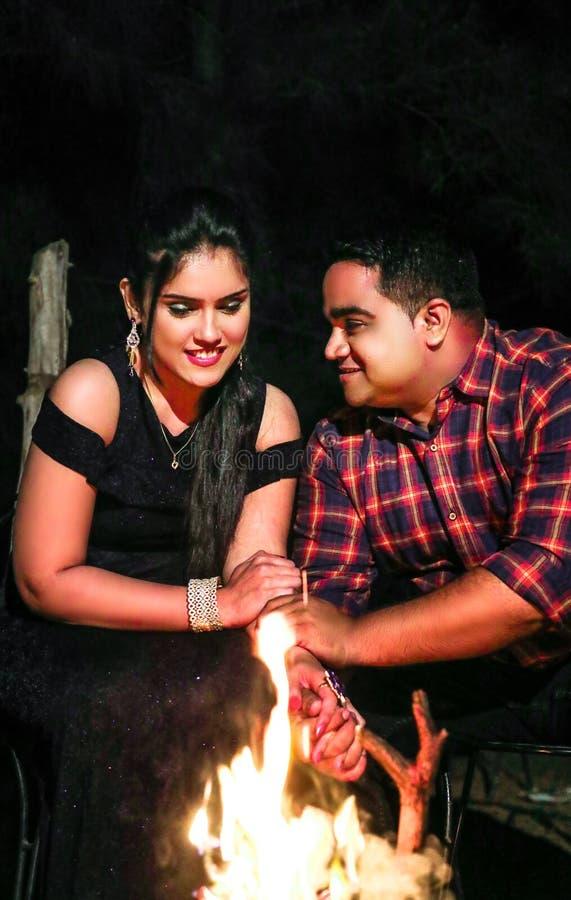 Tempo de lazer romântico da despesa dos pares perto da fogueira na noite imagem de stock royalty free