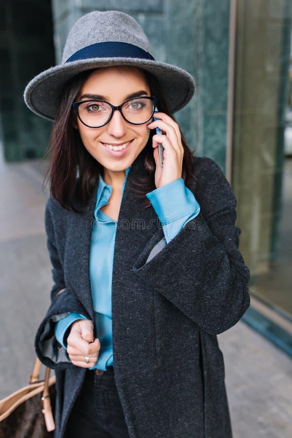 Tempo de trabalho ocupado da jovem mulher elegante no revestimento cinzento, chapéu, vidros pretos andando na rua na cidade Discu fotos de stock