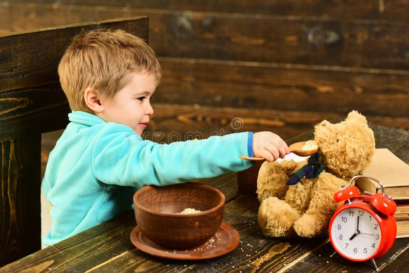 Tempo del pasto Il piccolo bambino e l'orsacchiotto hanno insieme pasto Amico del giocattolo dell'alimentazione del ragazzo con i fotografie stock libere da diritti