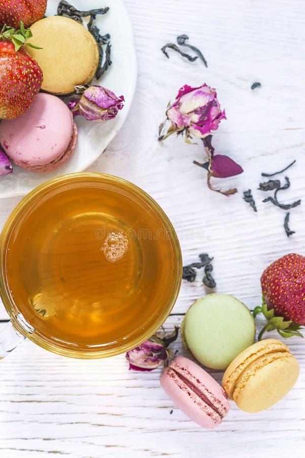 Tempo del tè con i maccheroni francesi: la tazza di tè, maccheroni francesi tradizionali, tè asciutto, è aumentato germogli s immagine stock libera da diritti