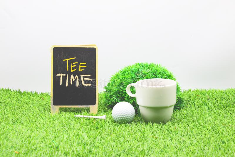 Tempo del tè per il giocatore di golf, segno e tazza e palla da golf di caffè su erba verde fotografia stock libera da diritti