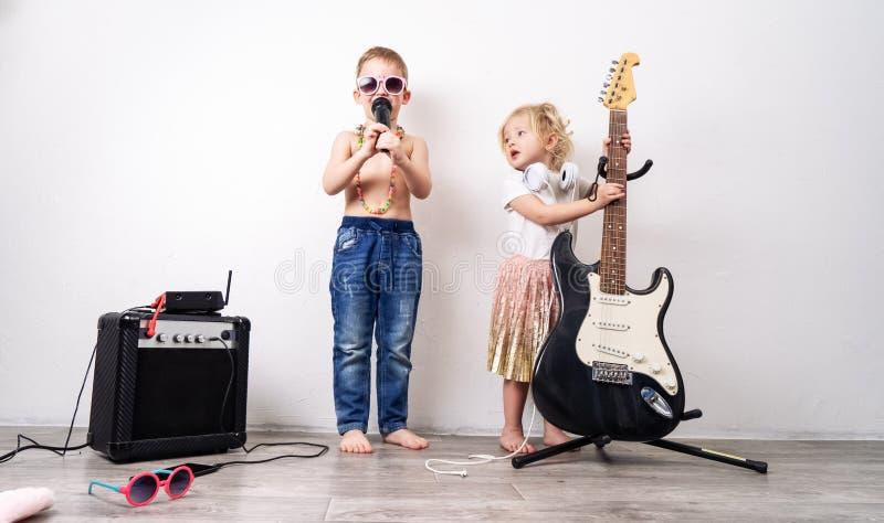 Tempo della famiglia: i bambini, un ragazzo e una ragazza, organizzano un concerto domestico e cantare con un microfono e una chi immagine stock libera da diritti