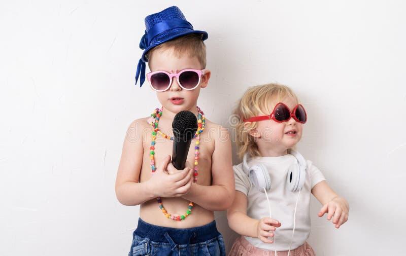 Tempo della famiglia: i bambini, un ragazzo e una ragazza, organizzano un concerto domestico e cantare con un microfono e una chi fotografia stock