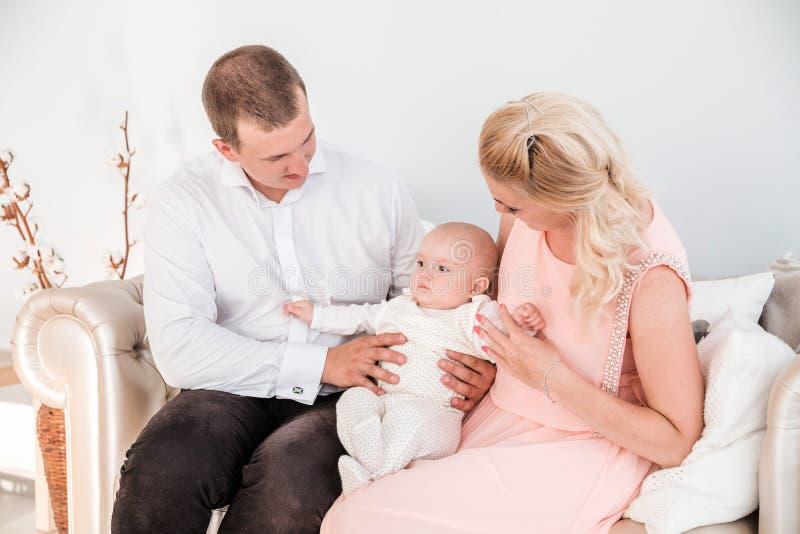 Tempo della famiglia Il papà e la mamma stanno sedendo sullo strato con il loro giovane figlio fotografie stock