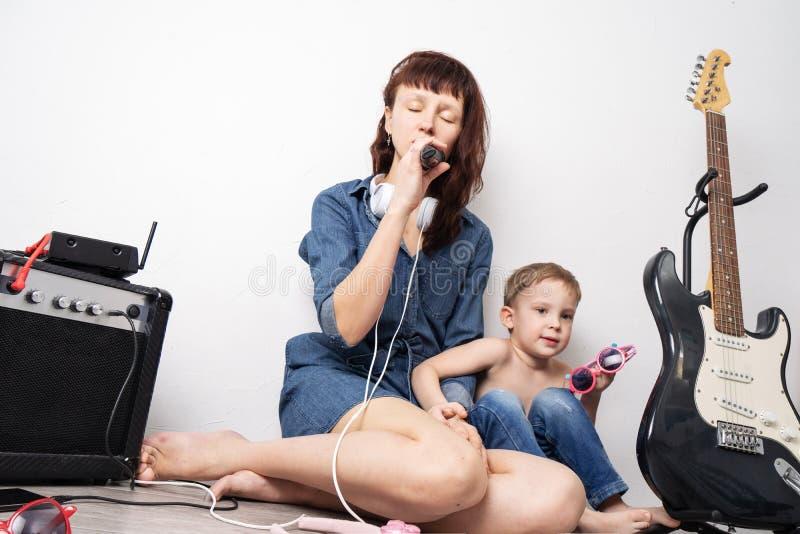 Tempo della famiglia: la madre con il figlio ha messo in scena un concerto domestico e canta con un microfono e una chitarra elet fotografia stock libera da diritti