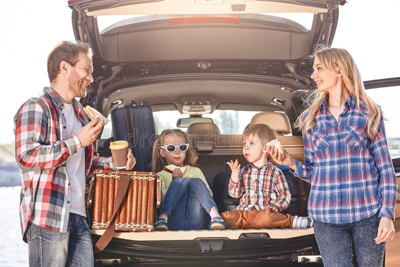 Tempo dello spuntino La famiglia sta vicino all'automobile, avendo un pranzo Viaggio stradale della famiglia immagini stock libere da diritti