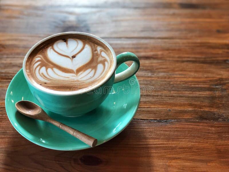 Tempo di distensione Caffè di arte del Latte in tazza verde e cucchiaio di legno immagine stock