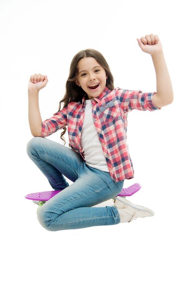 Tempo di guidare La ragazza del bambino eccitata si siede il bordo del penny Hobby teenager moderno Il fronte felice della ragazz fotografia stock