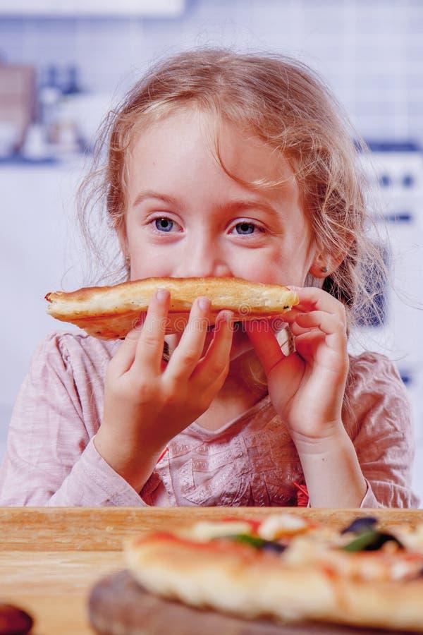 Tempo di mangiare! Piccola ragazza bionda sveglia con pizza Bambino felice divertendosi mangiando cena fotografia stock libera da diritti
