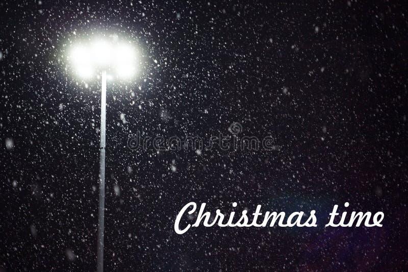 Tempo di natale Neve che cade alla luce di una lanterna fotografia stock