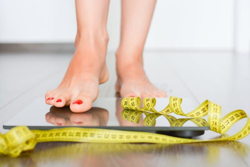 Tempo di perdere i chilogrammi con i piedi della donna che fanno un passo su una bilancia immagini stock