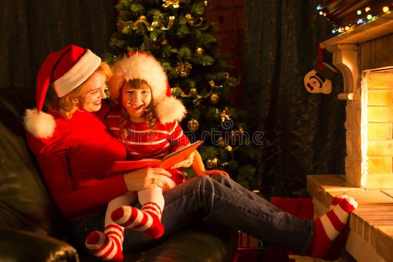 Tempo di storia di Natale con la madre ed il bambino dentro immagini stock libere da diritti