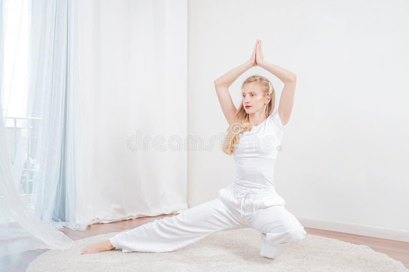 Tempo di yoga La bella donna sta praticando l'yoga a casa immagine stock