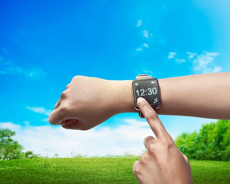 Tempo do ajuste da mão no smartwatch foto de stock