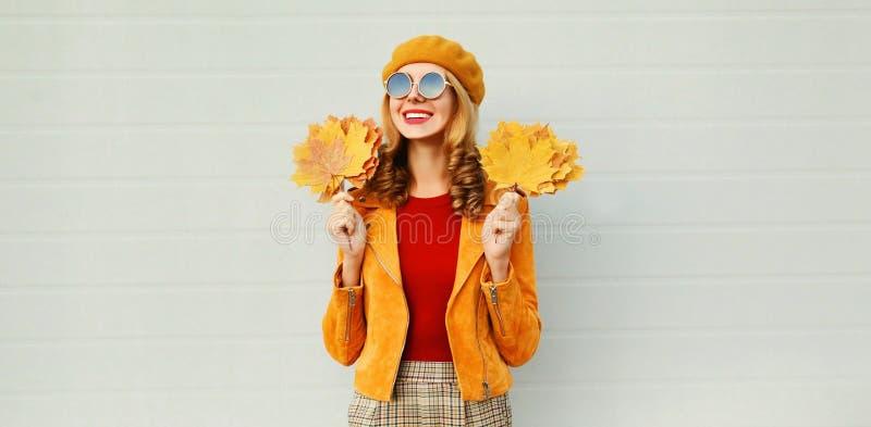 Tempo do outono! mulher de sorriso bonita com as folhas de bordo amarelas que olham afastado na rua da cidade sobre a parede cinz foto de stock