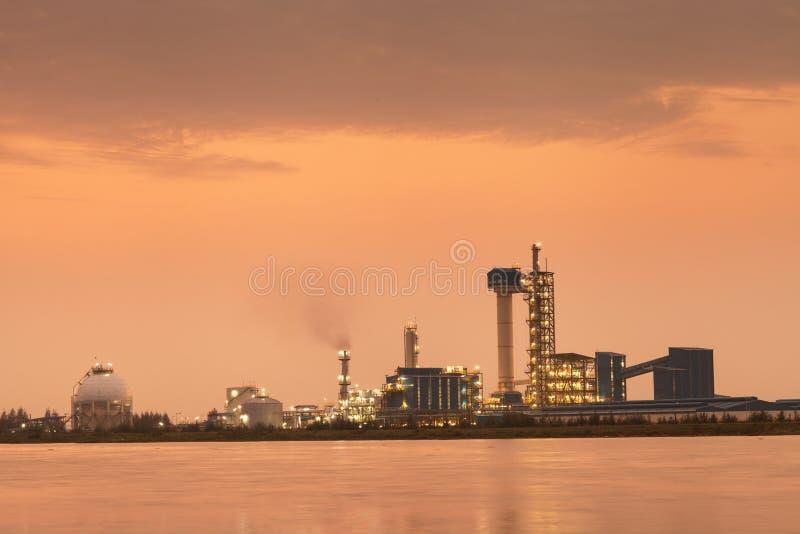 Tempo do por do sol da refinaria de petróleo com reflexão, instalação petroquímica imagem de stock royalty free