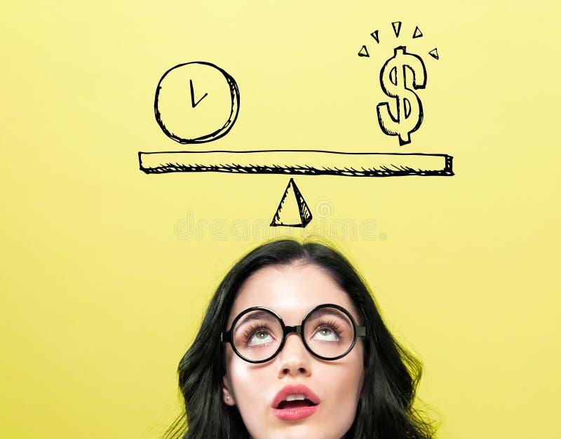 Tempo e dinheiro na escala com jovem mulher imagem de stock
