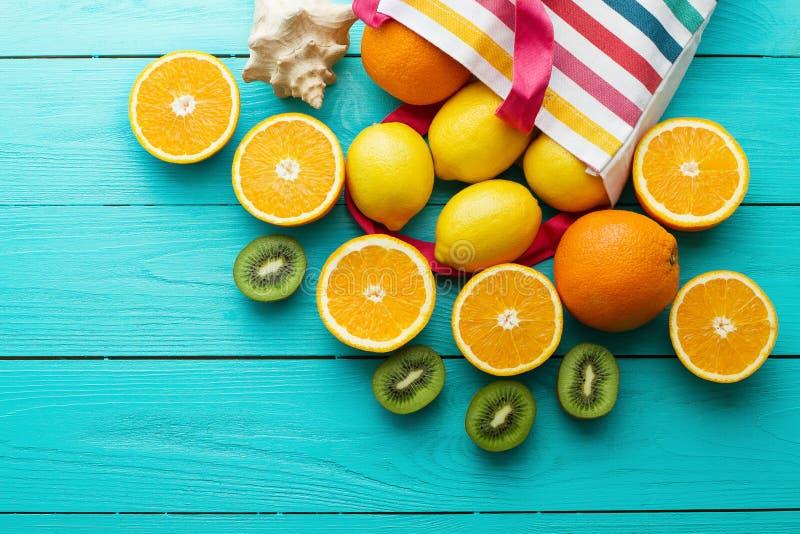Tempo e frutti di divertimento di estate su fondo di legno blu Derisione alta e pittoresca Arancia, limone, kiwi in borsa e coper fotografia stock