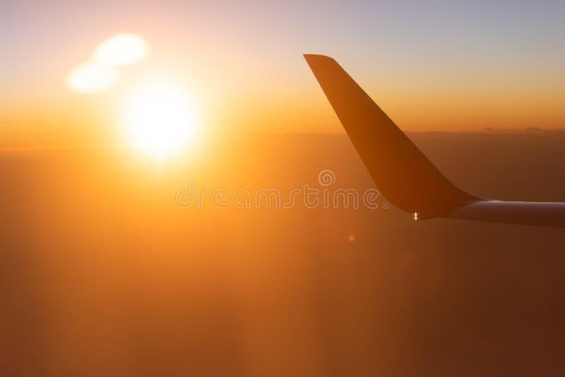 Tempo fantástico, vista cênico do assento de janela do avião, o ajuste do sol delicadamente em nuvens e skyline A asa do plano no fotos de stock