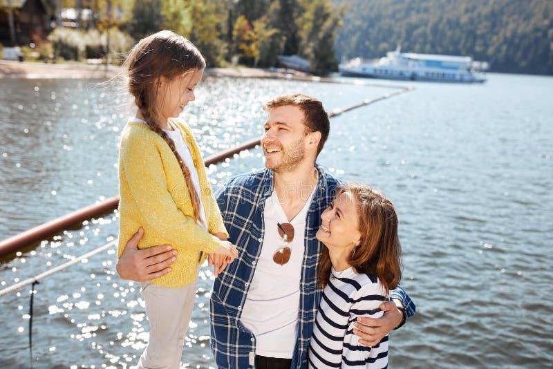 Tempo feliz da despesa da família junto fora perto do lago Pais que jogam com a filha que abraça e que tem o divertimento foto de stock royalty free