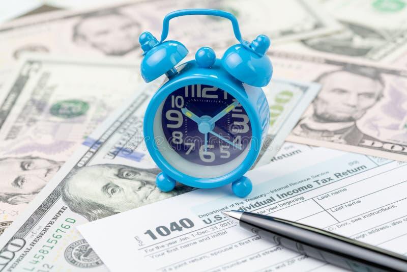Tempo o termine per il concetto annuale di presentazione di imposta, piccola retro sveglia miniatura con l'imposta sul reddito de fotografia stock libera da diritti