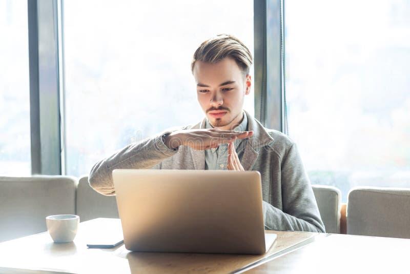 Tempo para fora! O retrato de advertir o freelancer novo farpado considerável no blazer cinzento está sentando-se no café e está  imagem de stock
