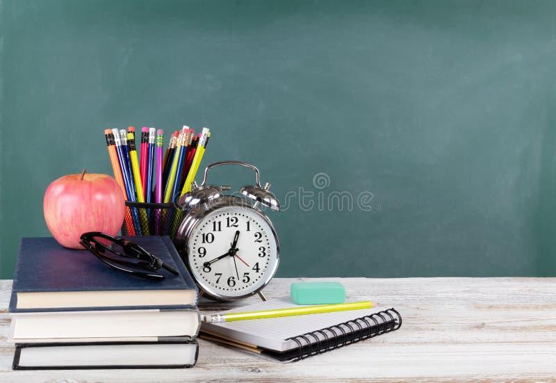 Tempo per di nuovo al concetto della scuola compreso i libri ed i rifornimenti della cancelleria con la lavagna verde nel fondo fotografia stock libera da diritti