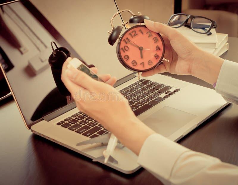 Tempo per il viaggio d'affari Impiegato di concetto che esamina un orologio pronto a decollare immagini stock