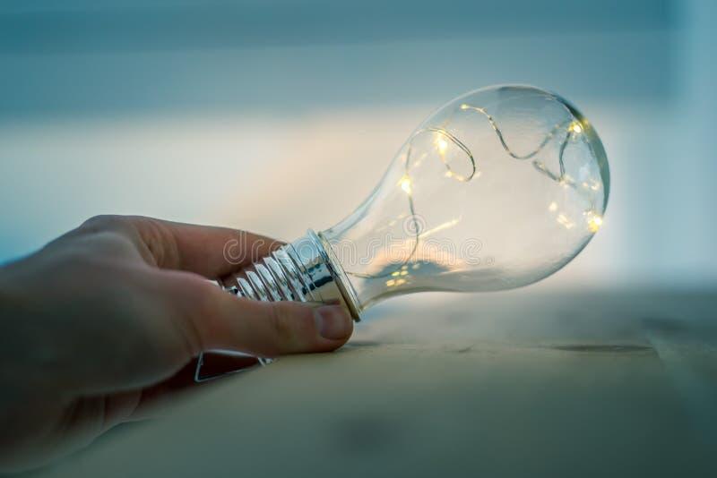 Tempo per le idee, l'ispirazione e l'invenzione: Le mani stanno tenendo una lampadina del LED fotografia stock libera da diritti