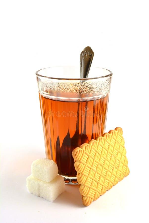 Tempo per tè con un biscotto e uno zucchero immagine stock