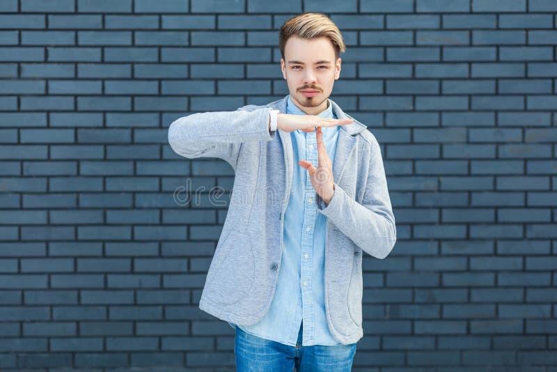 Tempo Retrato do homem louro novo considerável sério na posição do estilo ocasional com mão do gesto do intervalo e em olhar a câ imagem de stock