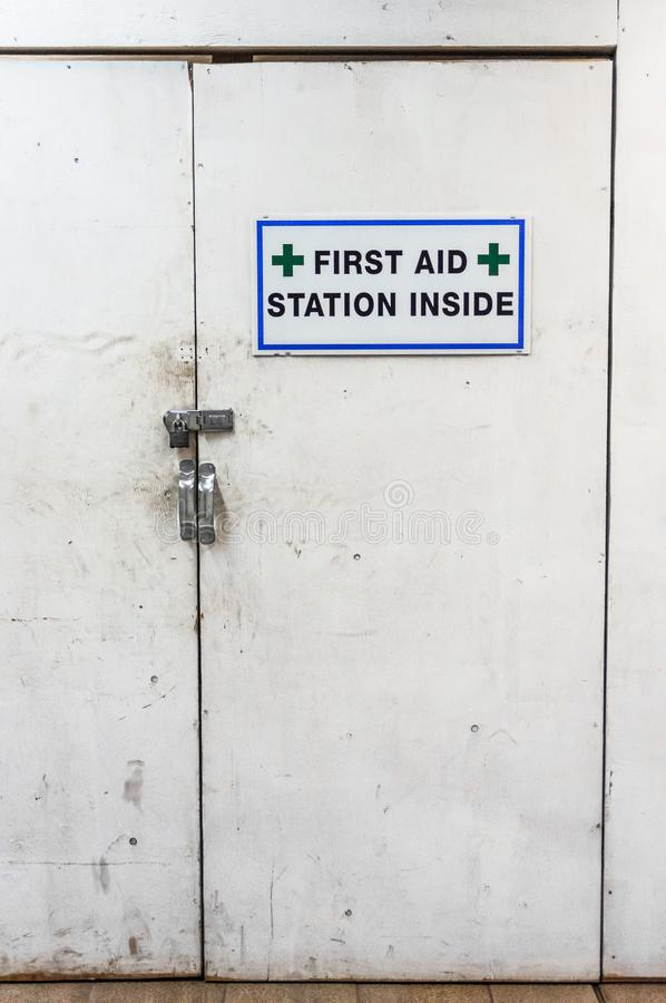 Temporary first aid station dirty white doors and sign at construction site. royalty free stock photography