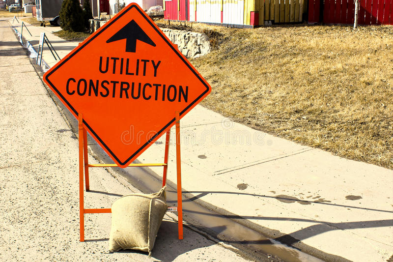 Temporary utility construction ahead sign beside a sidewalk stock photography