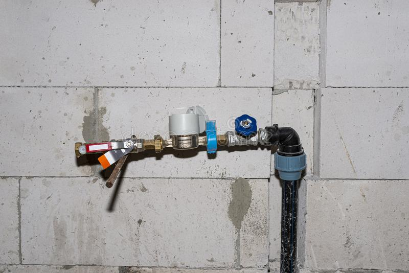 A temporary water valve with a meter connected to a pvc pipe, installed in a built house, against the wall. royalty free stock image