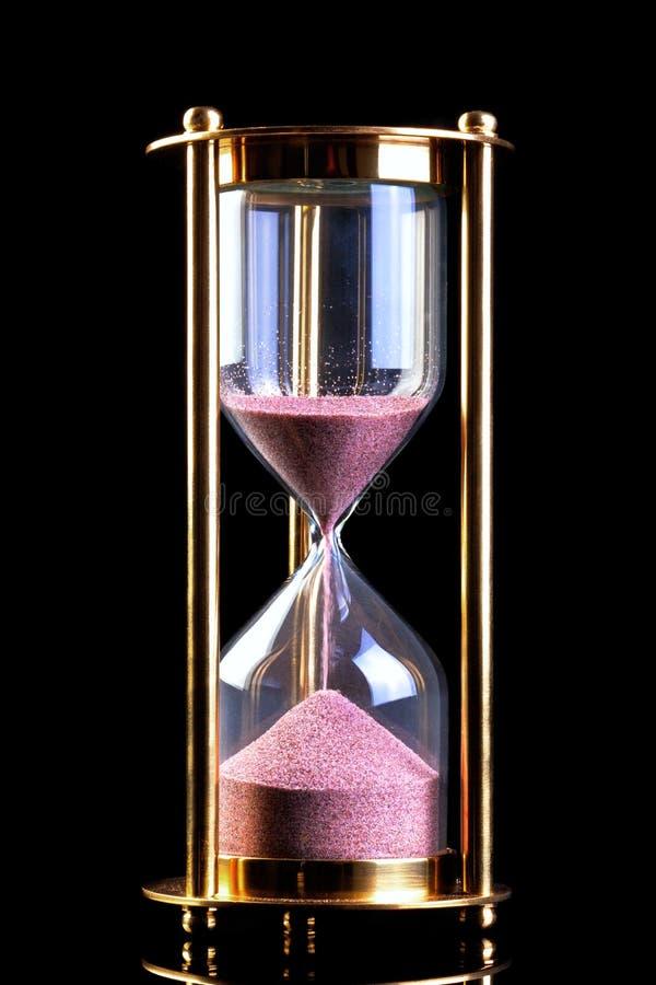 Temporizador de la arena del reloj de arena en negro imagenes de archivo