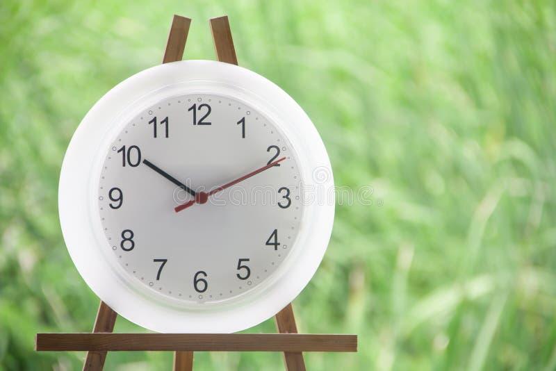 Temps blanc de l'exposition dix d'horloge sur le fond de jardin photo libre de droits