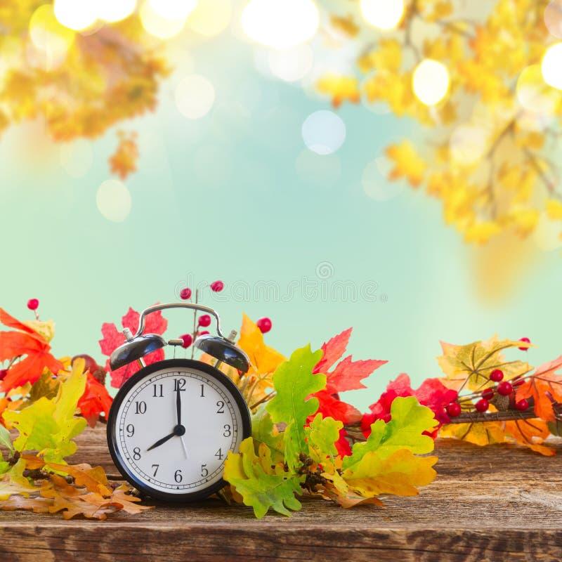Temps d'automne - feuilles de chute avec l'horloge images libres de droits