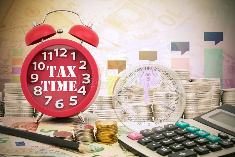 Temps d'impôts de mot écrit sur une horloge avec la boussole, les pièces de monnaie et le Calcula image libre de droits