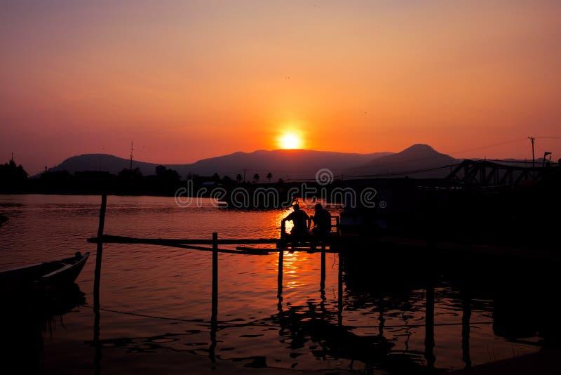 Temps de coucher du soleil sur la rivière Paysage orange de coucher du soleil avec le pilier et les hommes Vue orange vive de cie images libres de droits
