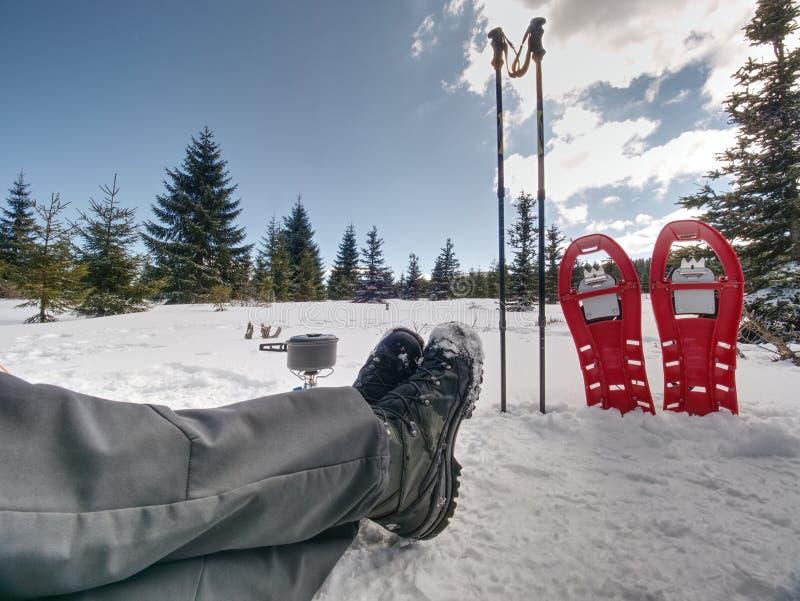 Temps de déjeuner pendant la traînée d'hiver Camper sur la neige et cuisson Raquettes rouges image stock