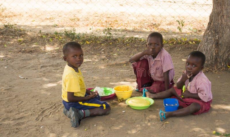 Temps de déjeuner de trois écoliers au Kenya photographie stock libre de droits