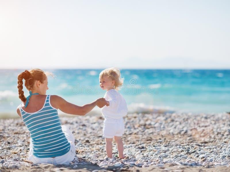 Temps de dépense de mère avec la chéri sur la plage images libres de droits