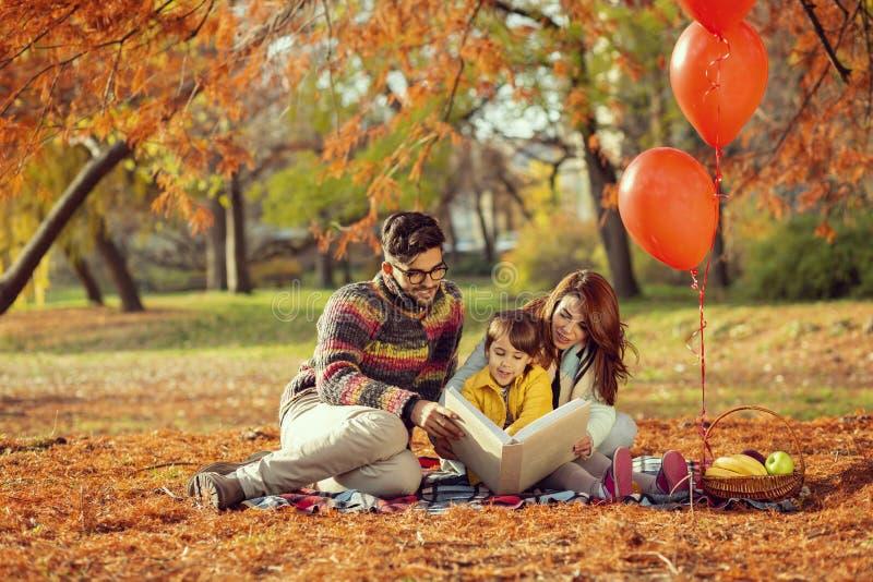 Temps de fabulation sur un pique-nique d'automne de famille en parc photographie stock libre de droits