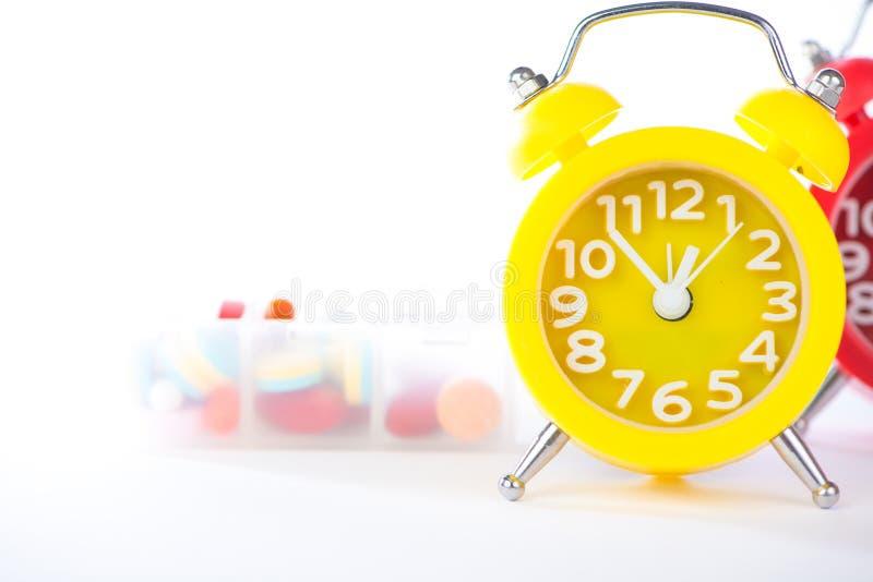 Temps de médecine d'exposition de réveil et de boîte de pilule photographie stock