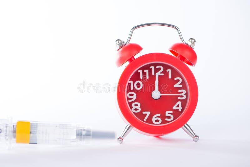 Temps de médecine d'exposition de réveil et de seringue d'injection photographie stock