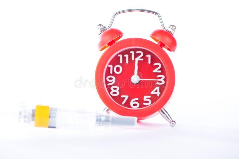 Temps de médecine d'exposition de réveil et de seringue d'injection photographie stock libre de droits