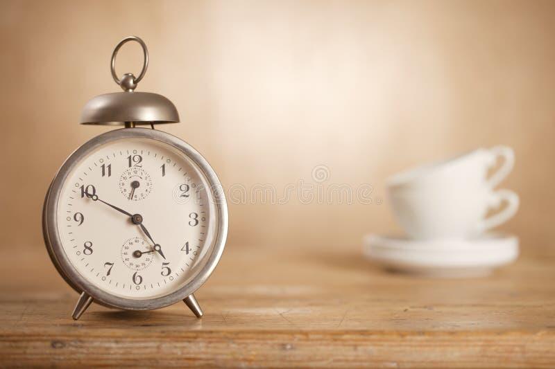 temps de thé de à 5 heures, cuvettes de thé blanches de rétro alarme photos libres de droits