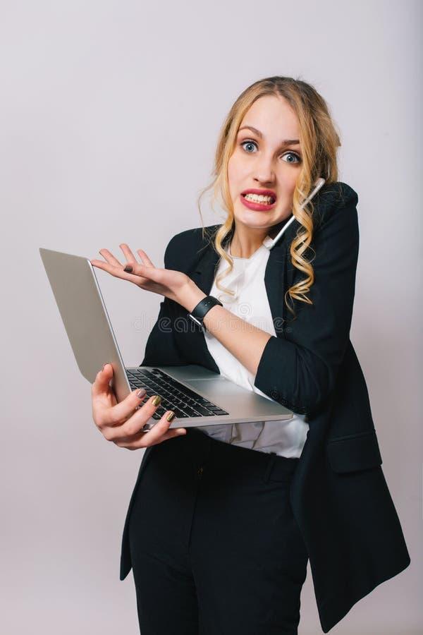 Temps de travail occupé de bureau de jeune femme blonde drôle étonnée dans la chemise blanche et la veste noire regardant la camé photographie stock libre de droits